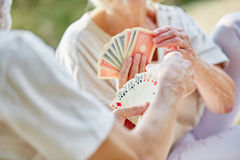 Two retired seniors playing cards as a hobby. In the garden in summer Royalty Free Stock Images