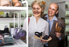 Two retirees together choosing pair of shoes in fashion store royalty free stock photos
