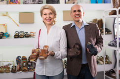 Two retirees together choosing pair of shoes in fashion store royalty free stock image