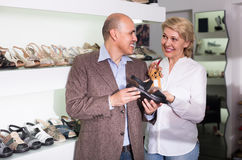 Two retirees together choosing pair of shoes in fashion store stock photography