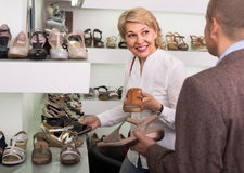 Two retirees together choosing pair of shoes in fashion store stock photos