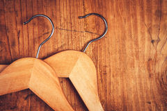 Two retro cloth hangers on rustic wooden background, top view Stock Photos