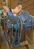 Two Retro Leather Horse Saddles. This veritcal image depicts two retro leather horse saddles, one brown and the other a light tan color, on sawhorses with Royalty Free Stock Images