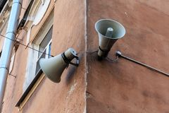 Two retro loudspeaker on an old building. Emergency citizen voice warning system stock photos