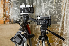 Two Retro Photo Cameras. On tripods, front shot with focus in the foreground Royalty Free Stock Image