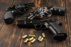 Cartridges, revolvers, pistols. Two revolvers, one pistol with cartridges on a wooden table Royalty Free Stock Photo