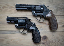 Two revolvers on a wooden. Two black revolvers on a wooden table Stock Images