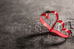 Two ribbon hearts on wood Stock Images