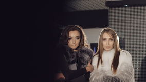 Two rich girls posing and catwalking in fur coats stock footage