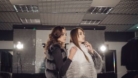 Two rich ladies posing in fur coats in boutique stock video footage