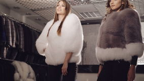 Two rich models posing in fur coats in fashionable boutique. In full HD stock video