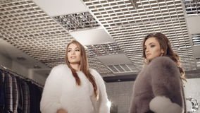Two rich women posing in fur coats in fashionable boutique. In full HD stock footage