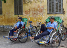 Two rickshaw drivers wait for customers. Royalty Free Stock Images