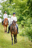 Two rider woman on horses going down from the hill Royalty Free Stock Photography