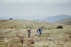 Two riders cyclists ride plain to mountains Royalty Free Stock Images