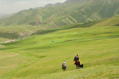 Two riders on horseback go away in the valley between the green mountains Royalty Free Stock Image