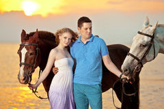 Two riders on horseback at sunset on the beach. Lovers ride hors Royalty Free Stock Photography