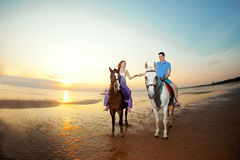Two riders on horseback at sunset on the beach. Lovers ride hors Stock Images