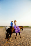 Two riders on horseback at sunset on the beach. Lovers ride hors Royalty Free Stock Image