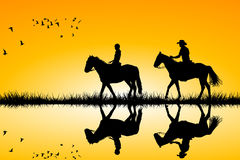 Two riders on horses standing together on sunset. Silhouettes of two riders on horses standing together on sunset Stock Photo