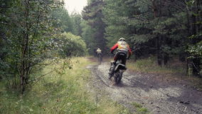 Two riders on motorcycles. Driving on a dirt road in woods during a race stock video footage