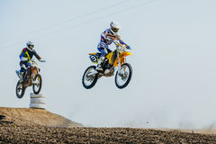 Two riders on motorcycles jump from mountain and fly Royalty Free Stock Photo