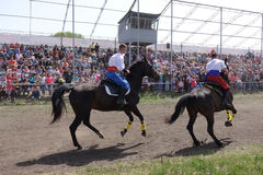 Two riders in national Ukrainian costumes ride horses on the track Stock Photos