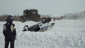 Two riders pass by the camera on a winter road. In the frame upside down car. A lot of snow stock video