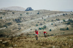 Two riders rider mountain bike rides on a mountain trail Royalty Free Stock Images