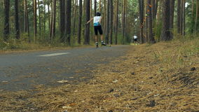 Two riders on ski-rollers ride woods. During competition in roller sports stock video