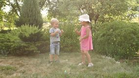 Two little children play in the Park in the summer. Two ridiculous children dance and show some movement of their hands in the park on the grass. Two little stock video footage