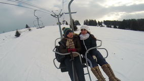 Two ridiculous girlfriends on the ski elevator, lift stock video