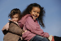 Two riding little girls Stock Photos