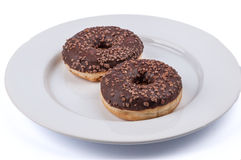 Two ring donuts with chololate glaze on white plate Royalty Free Stock Photos