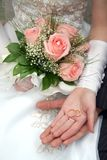 Two rings. On palms of a newly-married couple, a bouquet of roses in a hand Royalty Free Stock Images