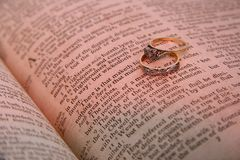 Two Rings. Two gold and silver rings on bible text with a shallow depth of field Stock Photos