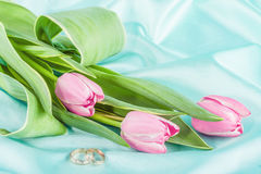 Two Rings And Tulips On A Turquoise Royalty Free Stock Image