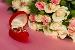 Two rings and a bouquet of roses Royalty Free Stock Photos