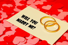 Two rings and a card with marriage proposal Royalty Free Stock Images