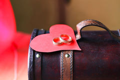 Two rings and a heart on antique box Stock Photos