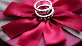 Two rings lie on a red bow. In Valentine`s Day stock video footage