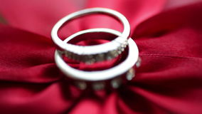 Two rings lie on a red bow. In Valentine`s Day stock video