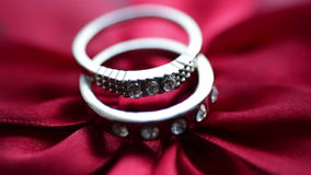 Two rings lie on a red bow. In Valentine`s Day stock footage