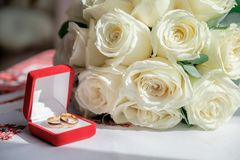Two rings in the red box and wedding bouquet on the table. Closeup view royalty free stock image