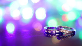 Two rings are on the table at the flashing multicolored background.  stock video