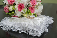 Two rings wedding, pillow in the shape of a heart, a bouquet of red and white roses. Stock Photo