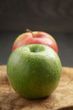 Two ripe apples on olive cutting board Stock Image