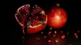 Two fruit grenades lie on a black table on a black background. Two ripe fruit pomegranate lie on a black table on a black background stock footage