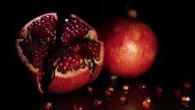 Two fruit pomegranates rotate on a black table on a black background. HD. Two ripe fruit pomegranates rotate on a black table on a black background. HD stock footage