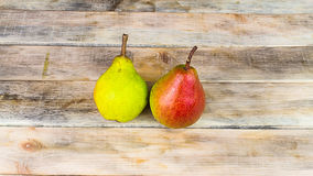 Two ripe green and red pears on rustic wooden background Stock Images